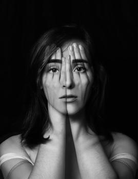 Photographie d'une femme se couvrant le visage.